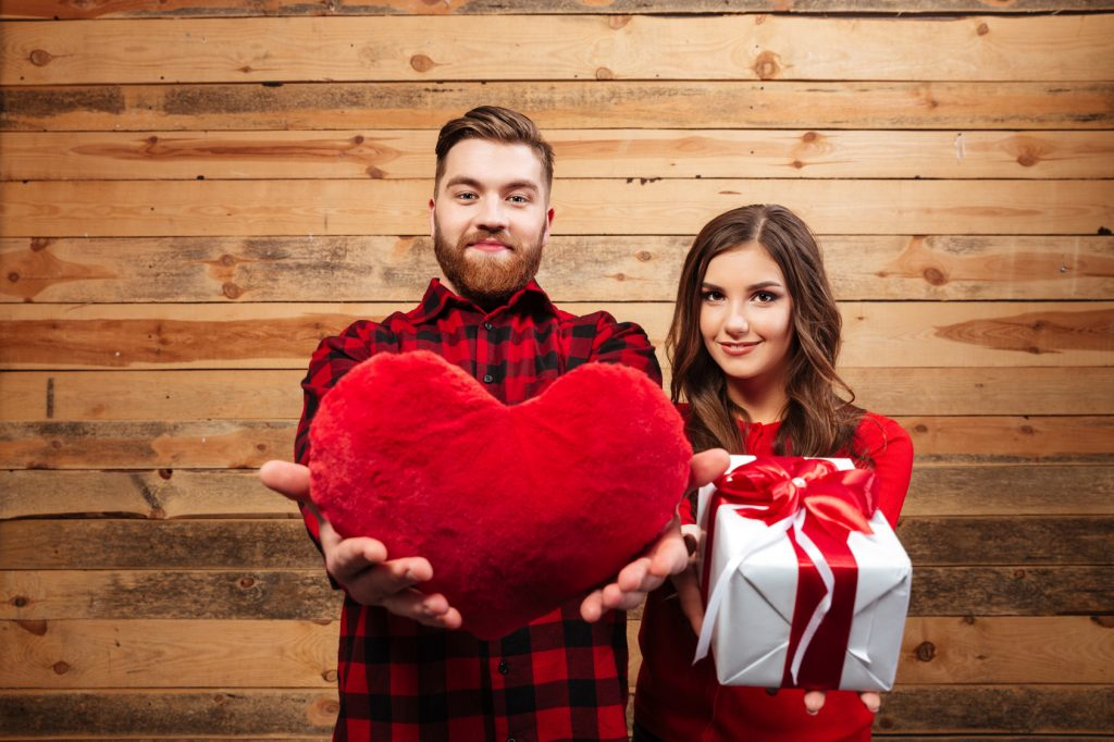 Couple with gift and heart. wooden background